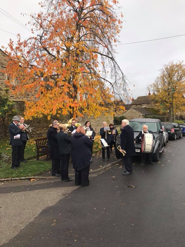 Cawthorne Brass Band stand to play under an autumnal tree