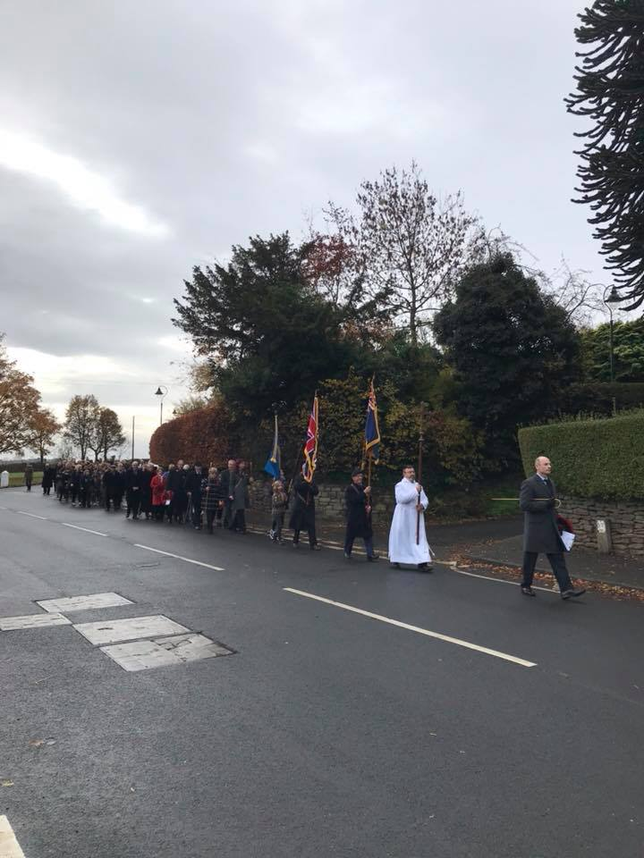 Church members parade down the road, bearing flags, following the Vicar and Parade Leader.