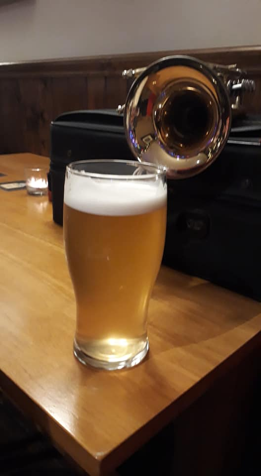 A picture of a pint of beer with a cornet in the background