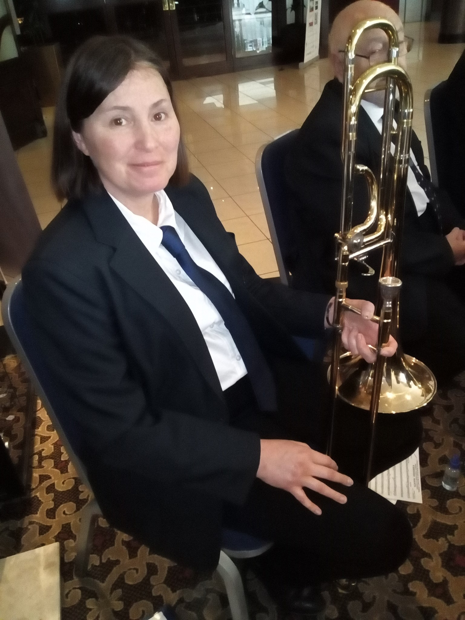 A woman sits, in band uniform, holding her Bass Trombone