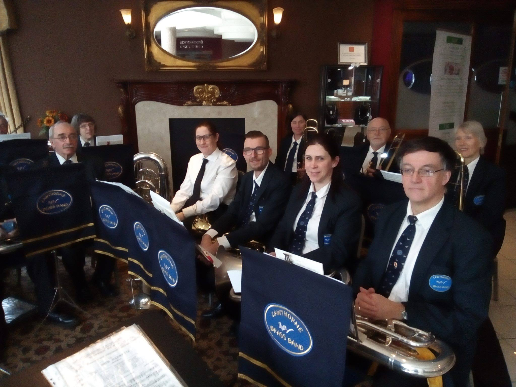 Band members wearing their uniforms are sat with their instruments on their laps