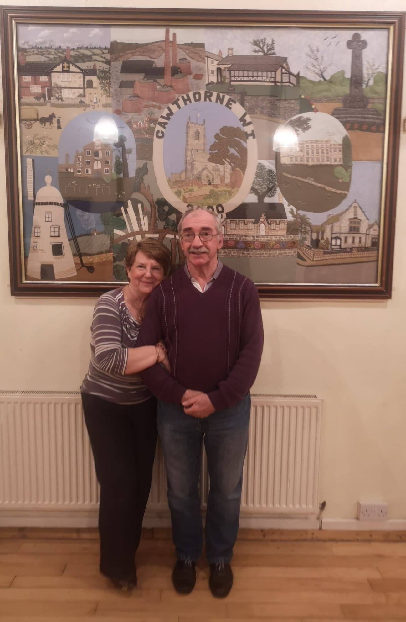 Alan and Christine stand in front of the Cawthorne WI tapestry