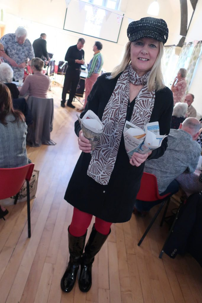 Rachel is wearing a sixties outfit including a black hat and boots and red tights. She is holding 3 newspaper cones of chips.