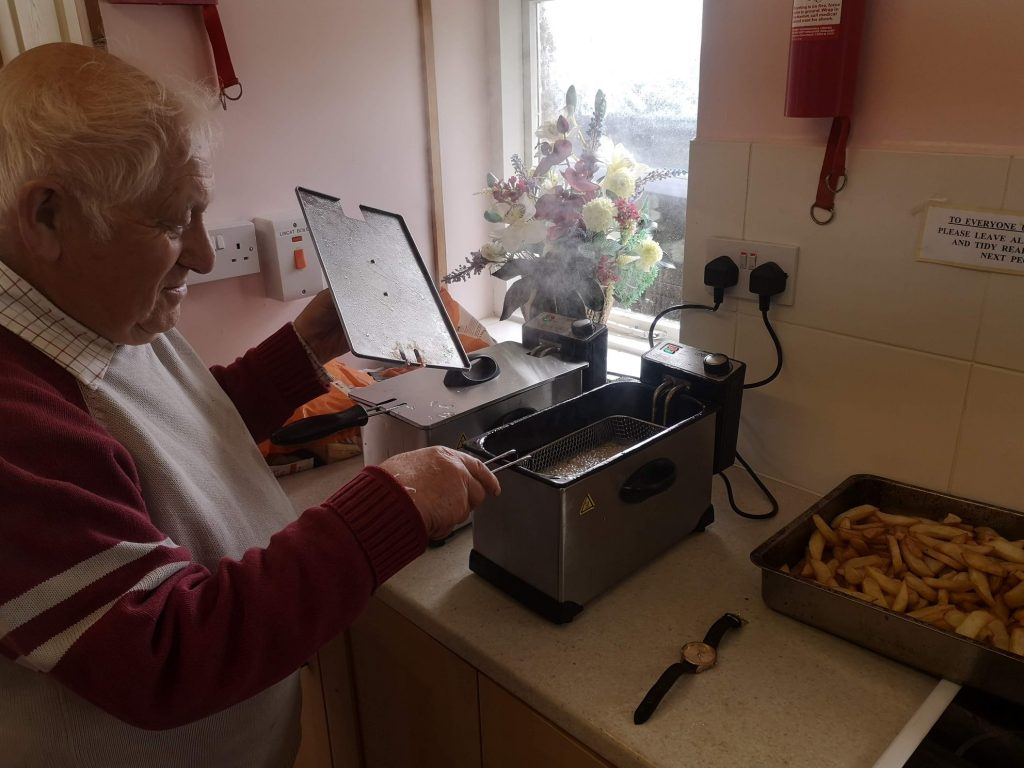 Elvin is frying chips in 2 small chip fryers. There is a tray of chips by the side.