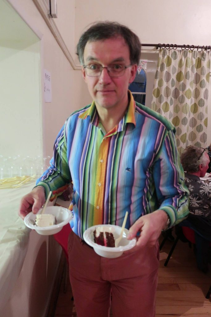 Nigel is wearing a stripy shirt and holding 2 bowls of Black Forest Gateaux