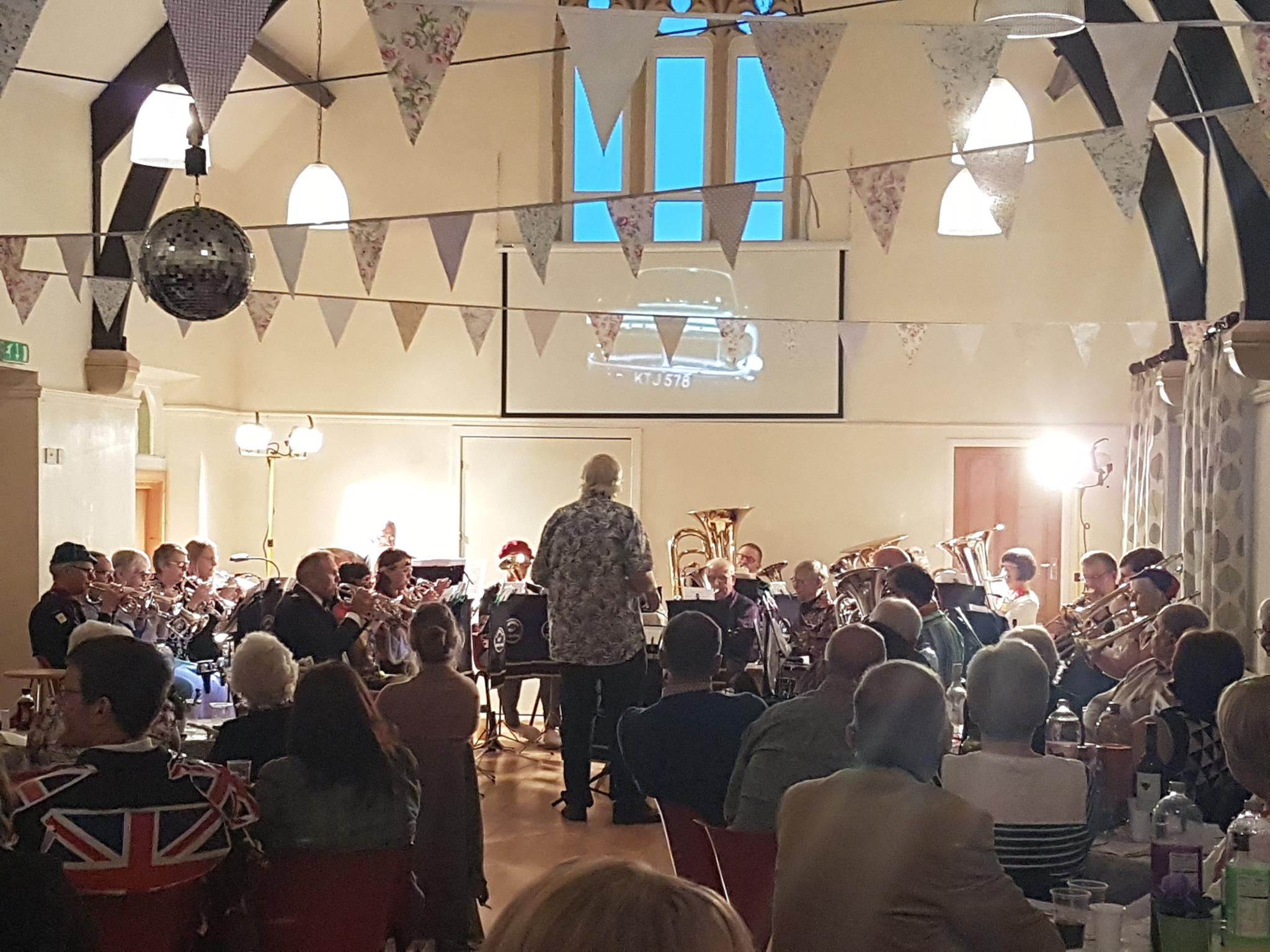 A shot of the band playing, taken from the back of the hall. You can see the bunting and glitter ball. the room is set for a party.