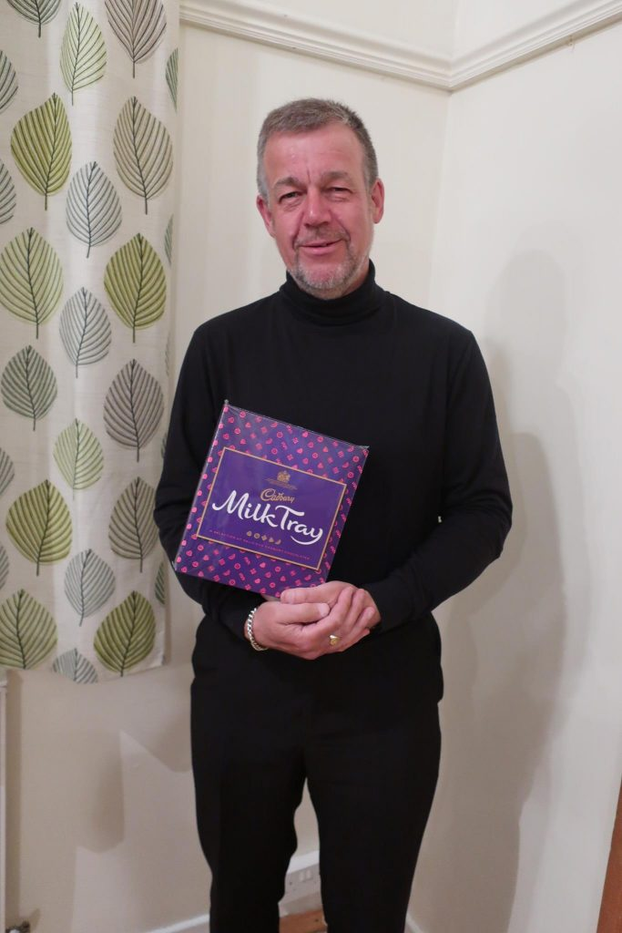 Martin is wearing all black and holding a box of milk tray