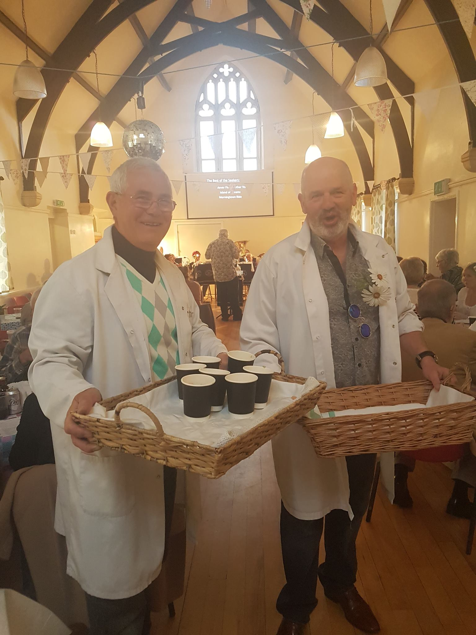 2 men in white coats hold trays with small pots of prawn cocktail