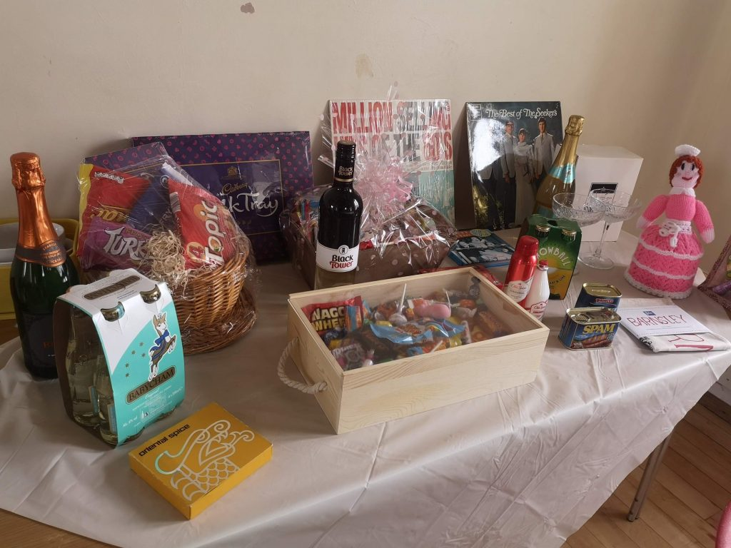 The raffle prizes laid out on a table, featuring LPs, 60s sweets, Babycham, Old Spice, a knitted toilet roll cover, and more