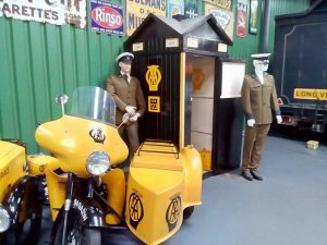A yellow motorbike and sidecar branded with the old AA logo