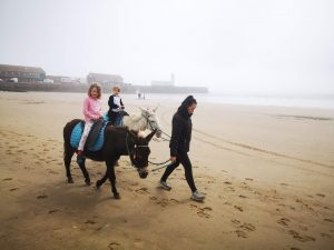 2 girls are riding donkeys which are being led along the beach
