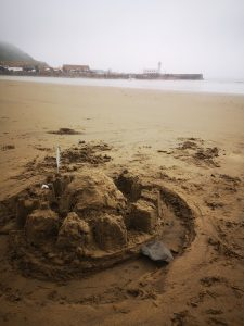 a sandcastle is in the foreground. There is a lighthouse in the mist in the background