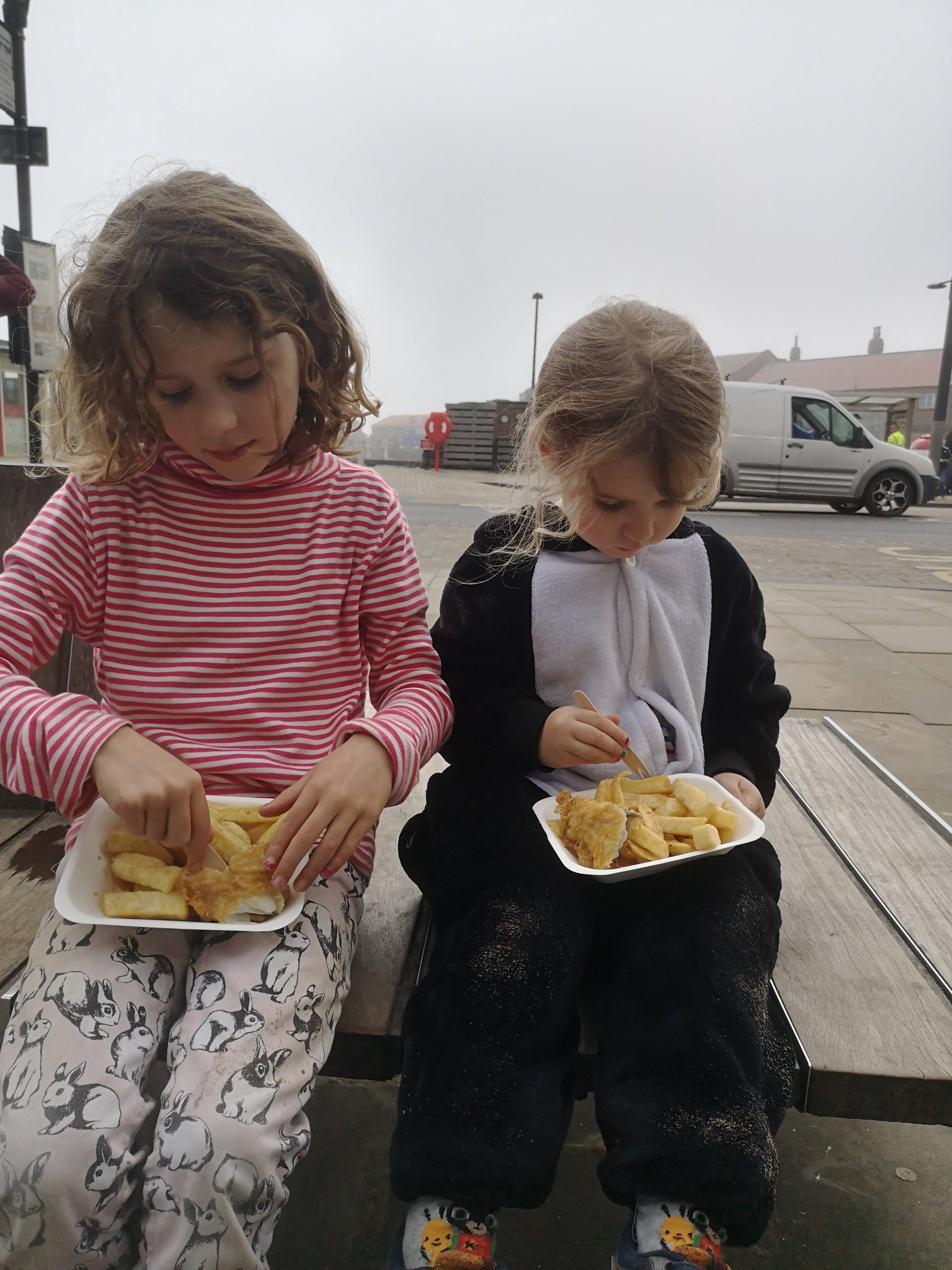 2 girls eat fish and chips from cartons