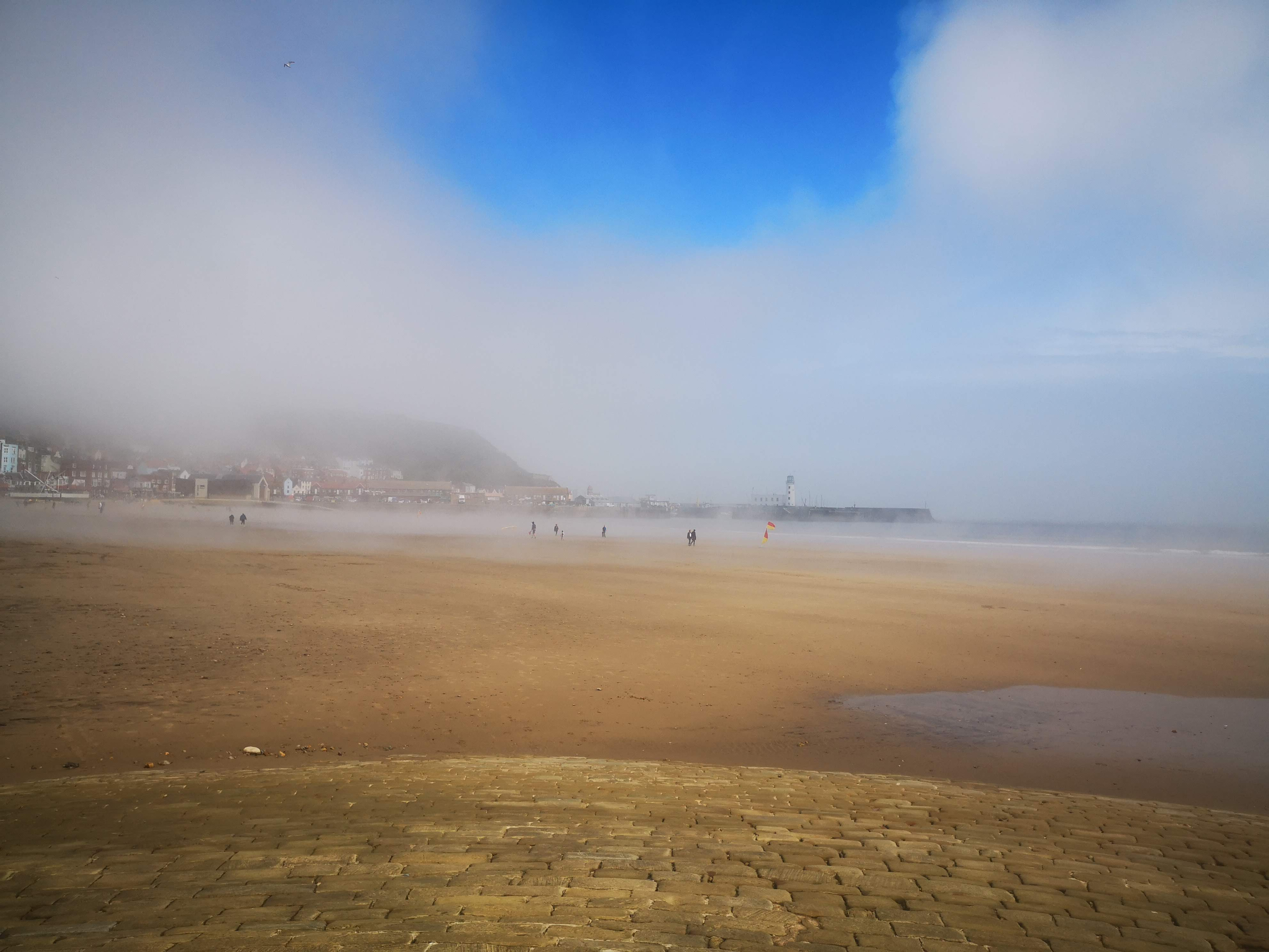 the beach is covered in mist but the sky is blue