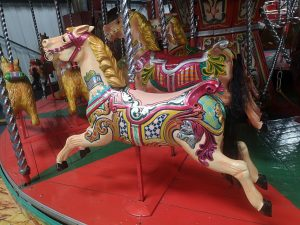 A close up of two carousel style horses