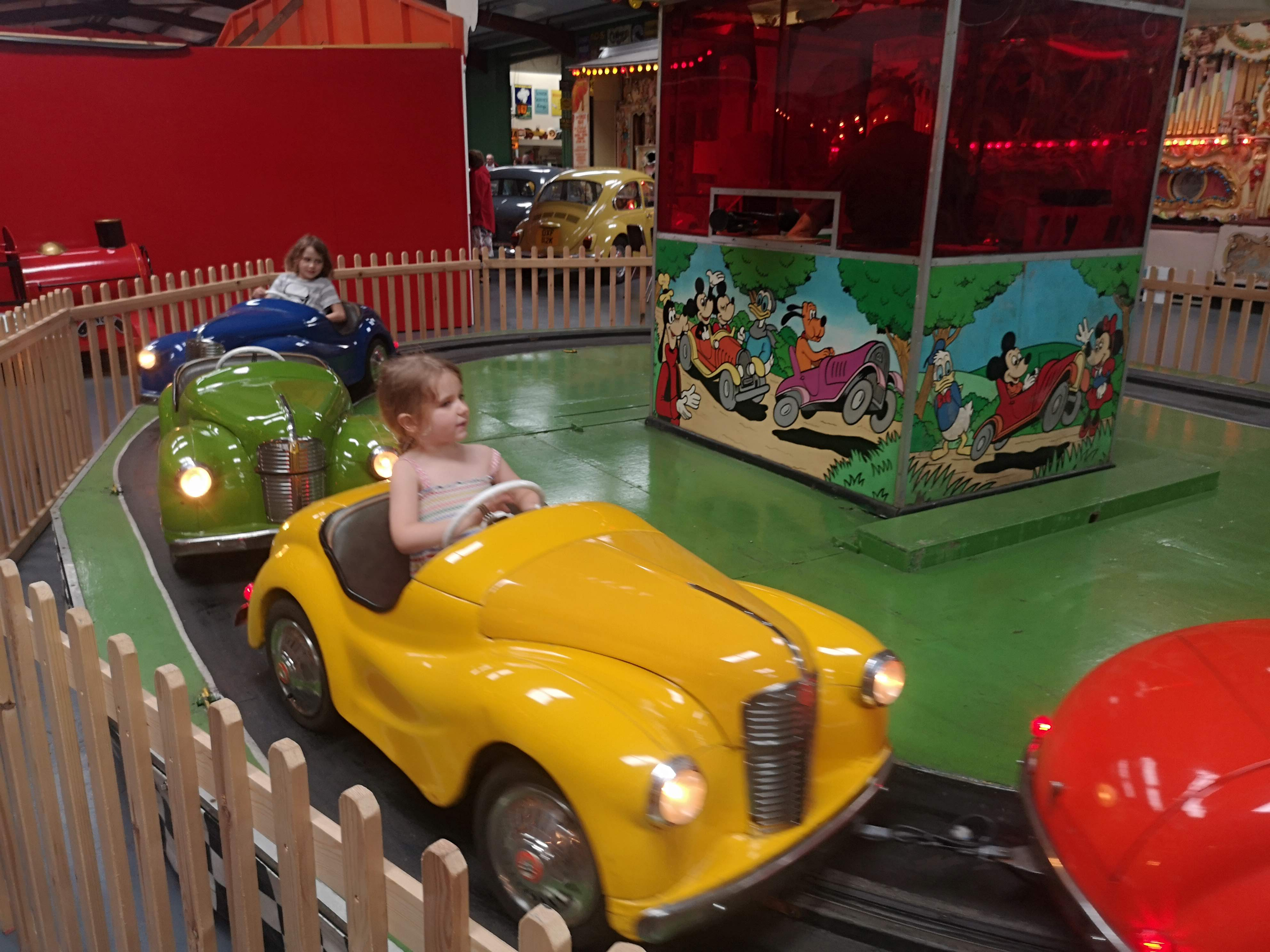 there are 4 little cars in primary colours. 2 girls ride in them happily