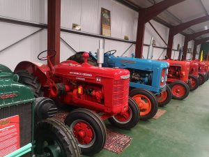 A row of old tractors, red, blue and red.