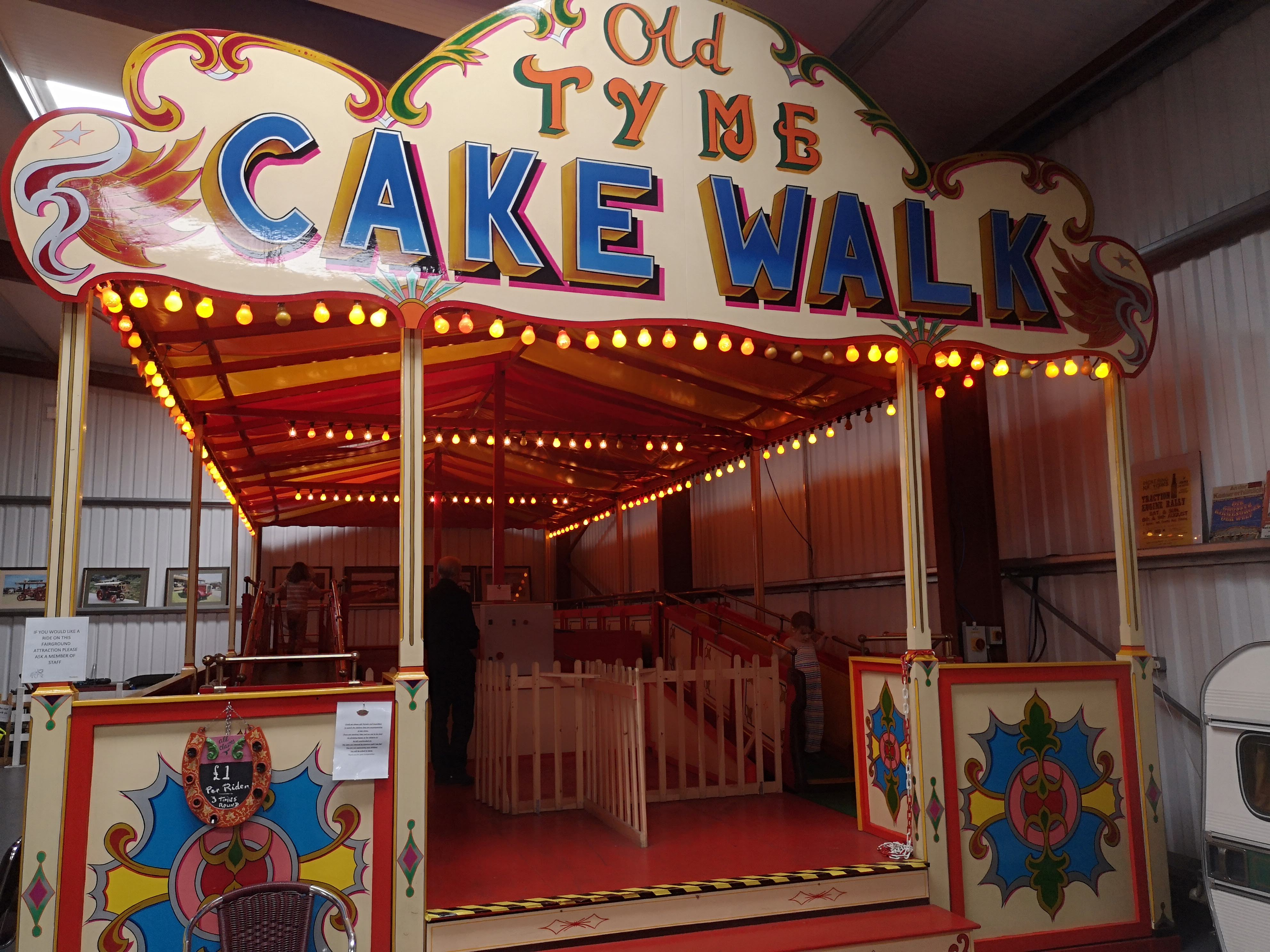 An old fair ground ride where there are moving walkways. 2 girls are walking around it