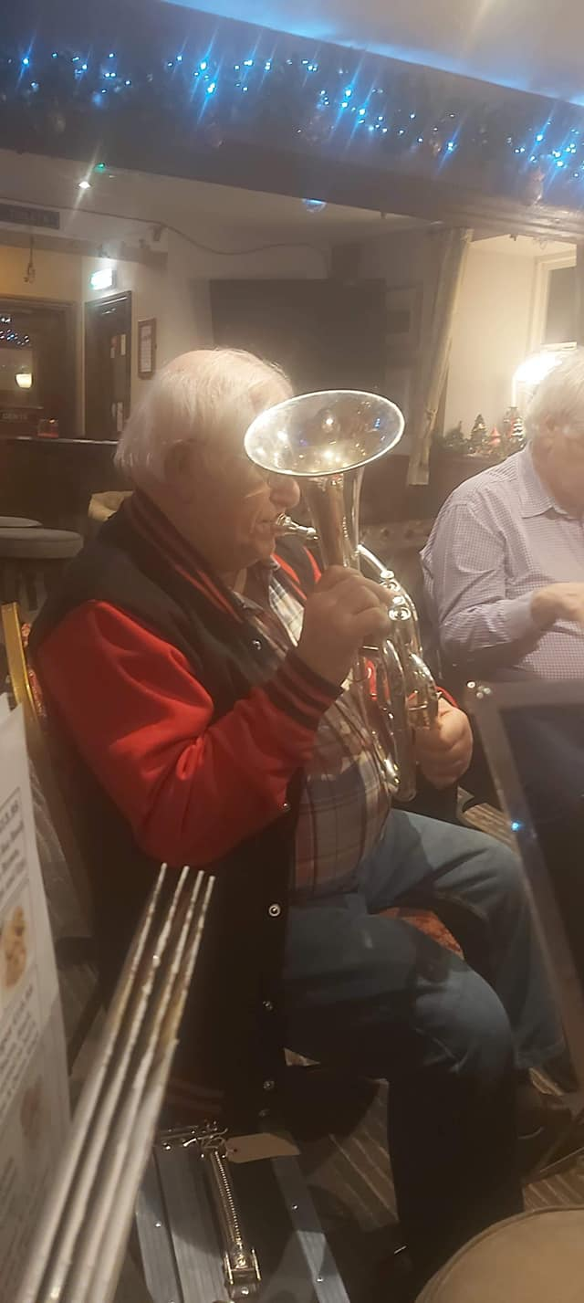 Elvin is playing the tenor horn, in a pub