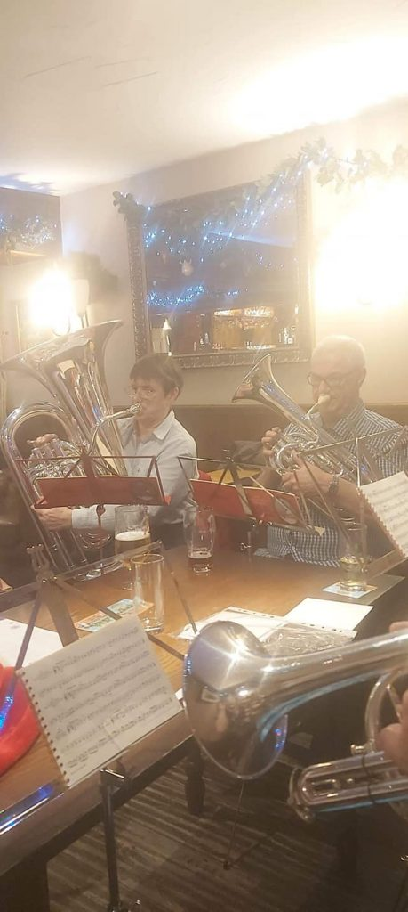 Band members play carols in a pub, wearing festive clothes