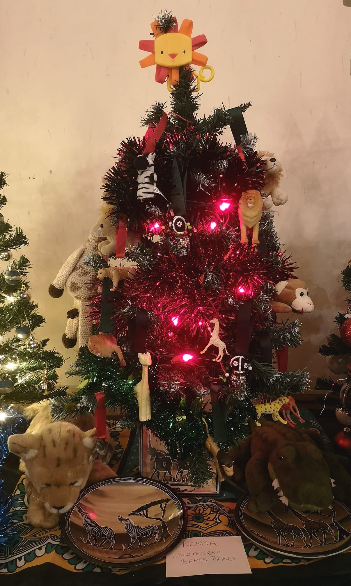 Small christmas tree decorated with black, green and red, the colours of the Kenyan flag, and many toy African animals.