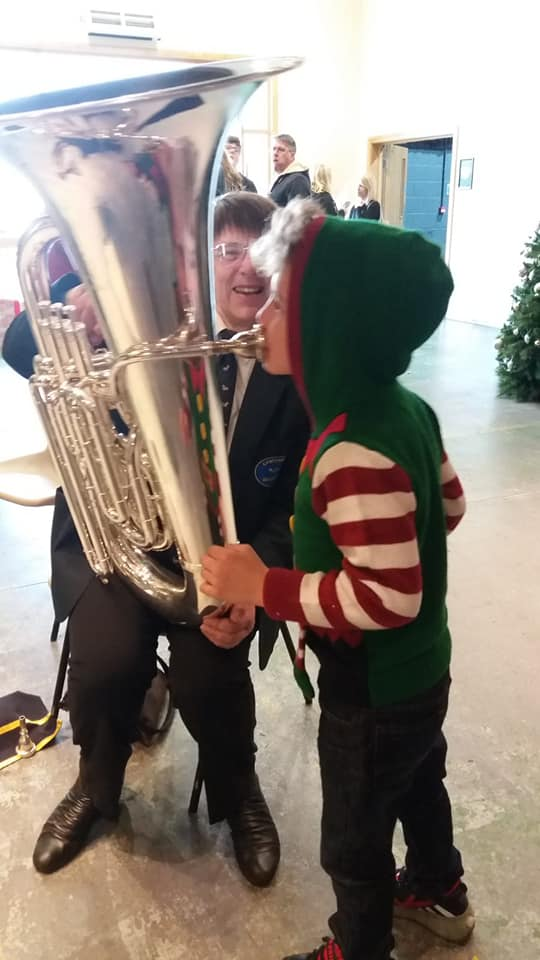A boy dressed as an elf plays the Bass while Margaret smiles in the background