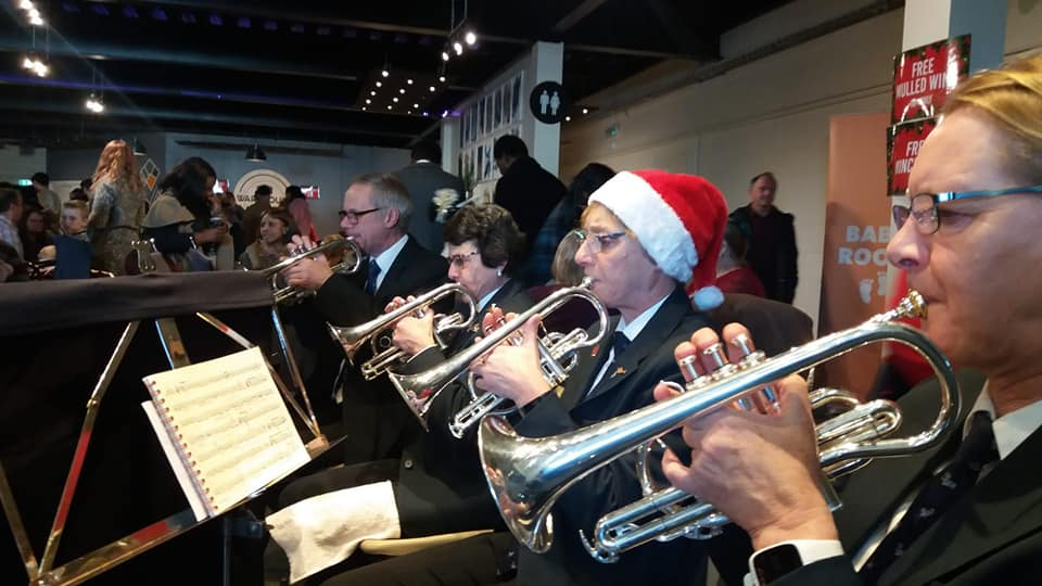 The cornet section are in uniform, one wears a Christmas hat.