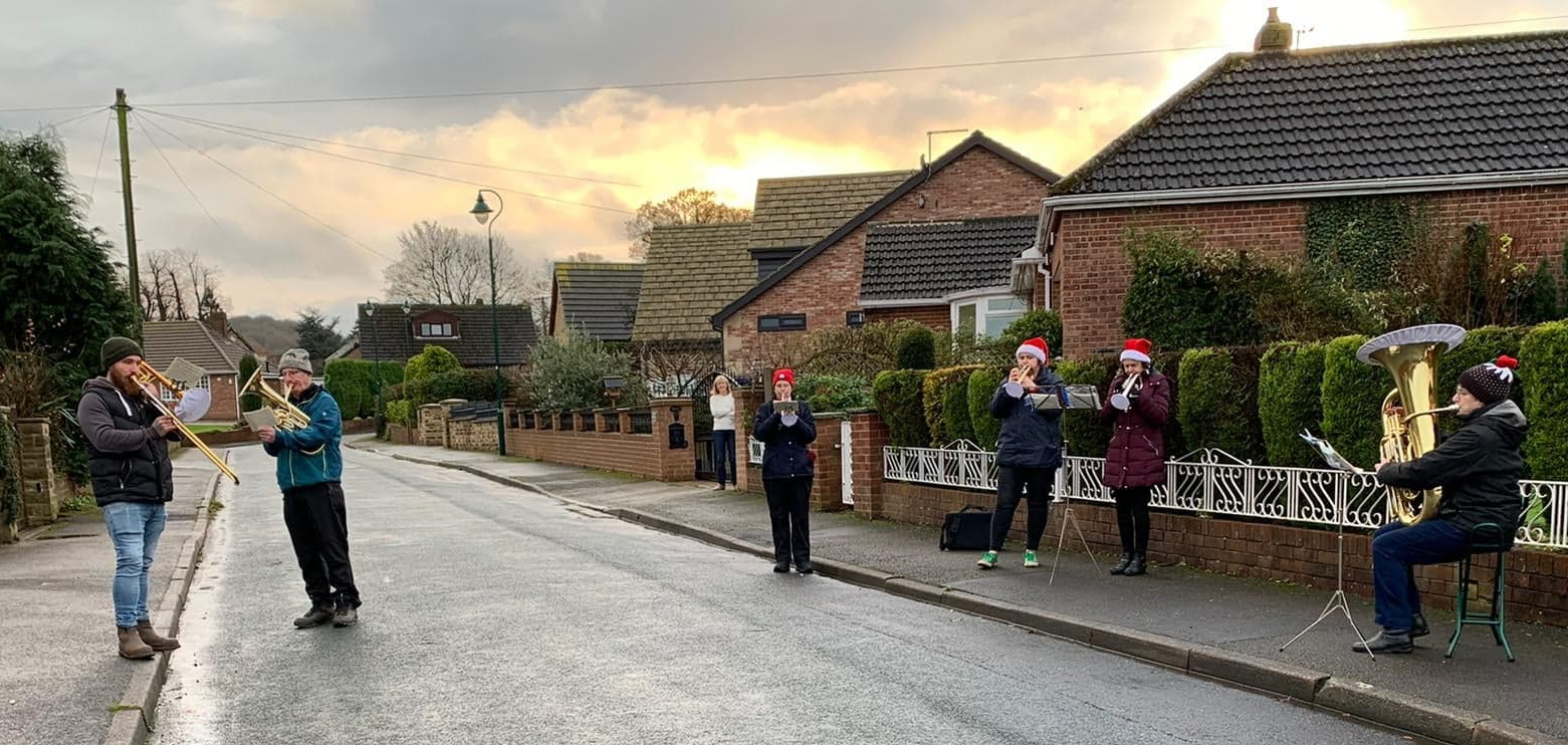 Members of Cawthorne Band are playing in a distanced line across the street. The sky is a beautiful yellow in the background - the beginning of sunset