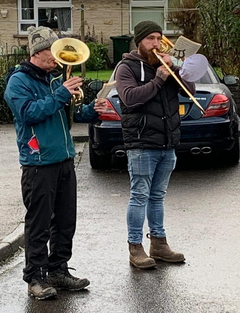 A baritone player and trombone player are tanding outside playing from music attached to their instruments by a lyre. They are wearing wooly hats.