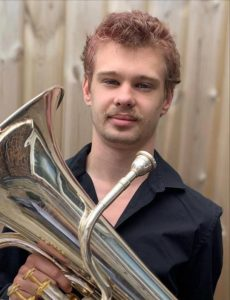 A young man wearing a black shirt is holding a euphonium and looking at the camera.