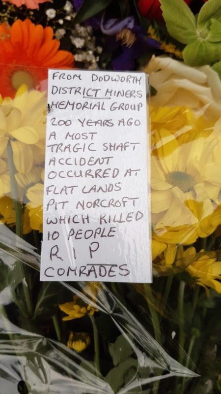 """A close up picture of the message written on the flowers. It reads """"From Dodworth District Miners Memorial Group. 200 years ago a most tragic shaft accident occurred at Flat Lands Pit Norcroft, which killed 10 people. RIP comrades"""""""