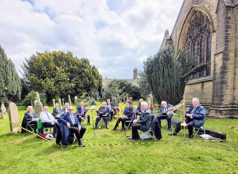 Members of Cawthorne Brass Band and Dodworth Colliery Band are sat in the grounds of the church, holding their instruments